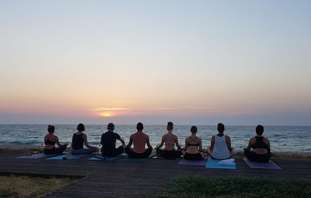 Yoga group on a beach in Corfu, with the sun setting over the sea's horizon